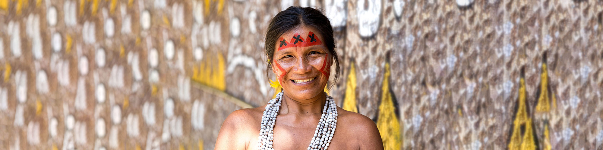 Guarani Translation Services Expert with Face Paint Near Painted Rocks